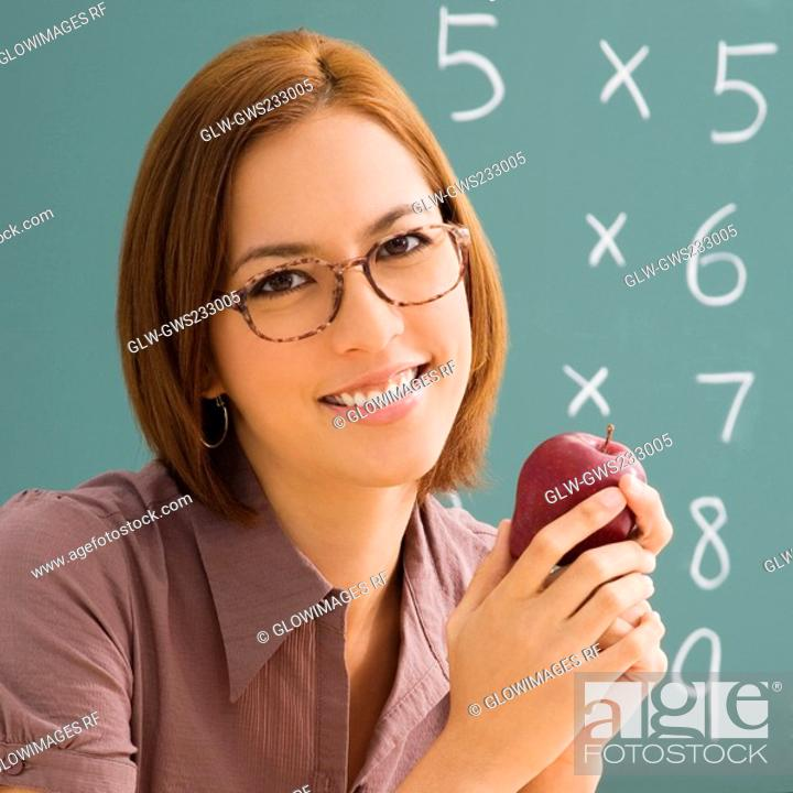Stock Photo: Portrait of a female teacher holding an apple and smiling.