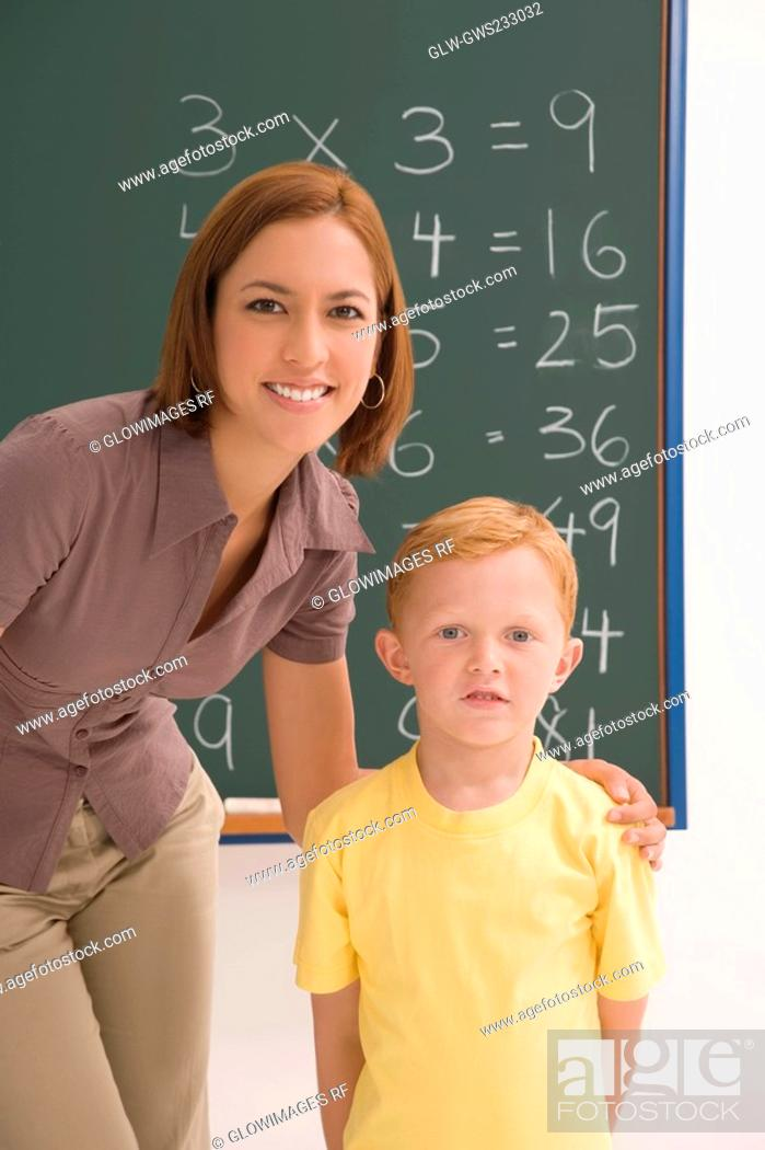 Stock Photo: Portrait of a schoolboy standing with his female teacher in a classroom.