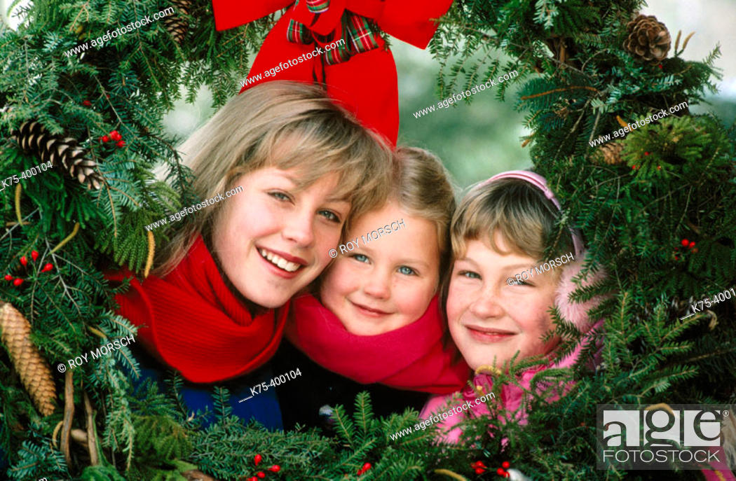 Stock Photo: Sisters framed by Christmas wreaths.