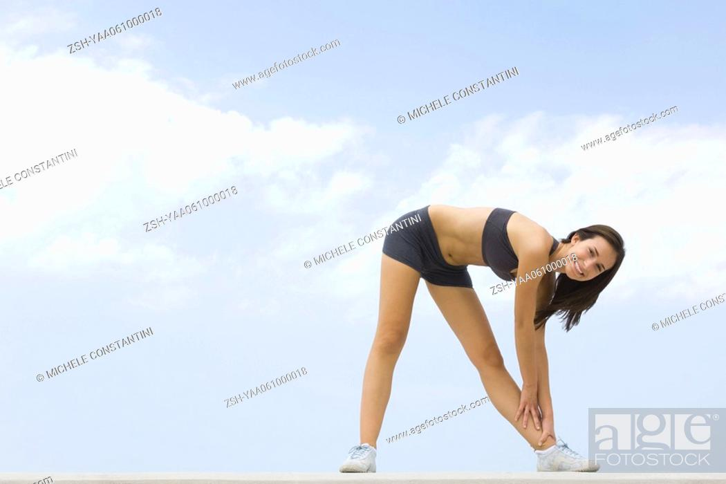 Stock Photo: Young woman bending over, touching ankle, smiling at camera.
