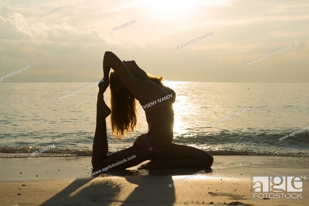 Stock Photo: Silhouette of a pigeon pose yoga on the beach.