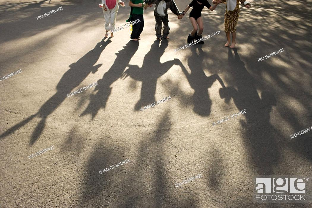 Stock Photo: Five children in fancy dress holding hands, casting shadow.