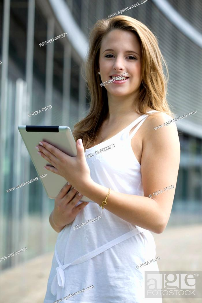 Stock Photo: Europe, Germany, North Rhine Westphalia, Duesseldorf, Young student with digital tablet, smiling, portrait.