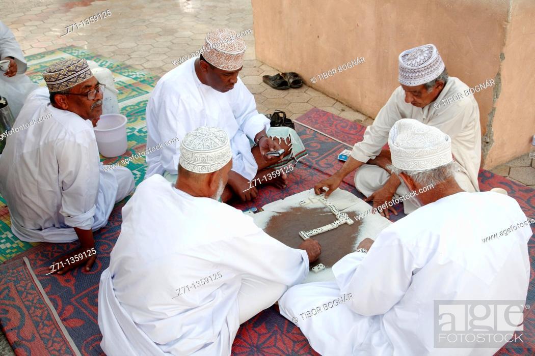 Stock Photo: Oman, Muscat, Mutrah, men playing dominoes.