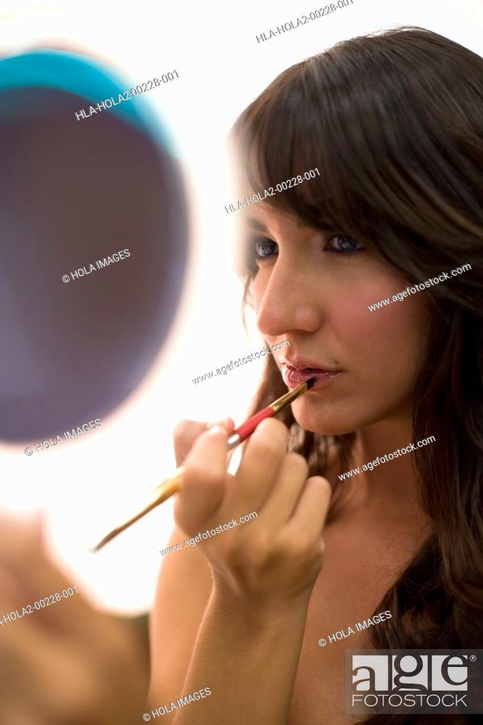 Imagen: Woman looking in mirror while applying lipstick.