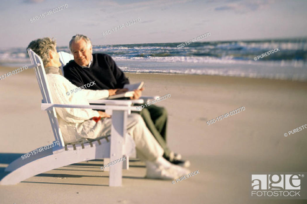 Stock Photo: Senior couple sitting together on the beach.