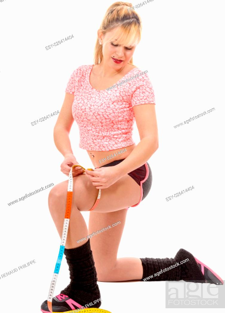 Stock Photo: a fitness sporty woman measuring her thigh with a measuring tape.