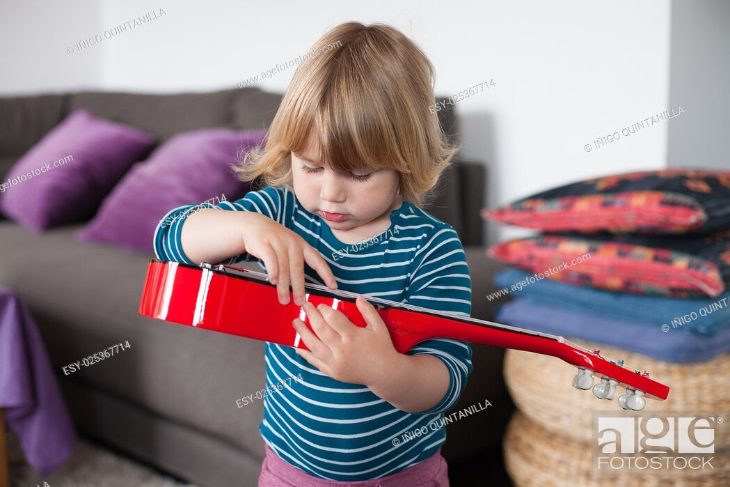 Stock Photo: blonde two years old child with striped blue and white sweater inside home playing with hand red spanish little guitar.