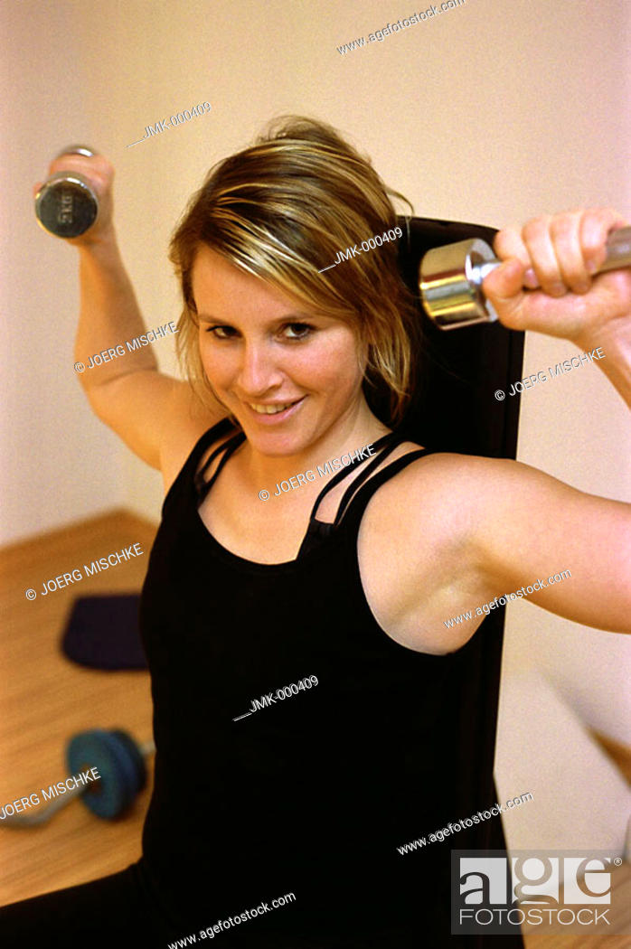 Stock Photo: Young woman at the gym, fitness center, doing some exercise with dumb-bells.