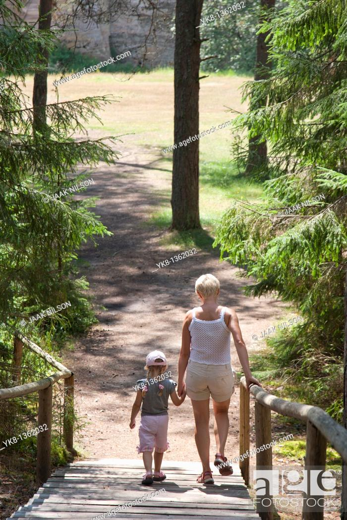 Stock Photo: Mother and Young Girl Walking on Boardwalk in Forest Holding Hands, Põlva County, Estonia.