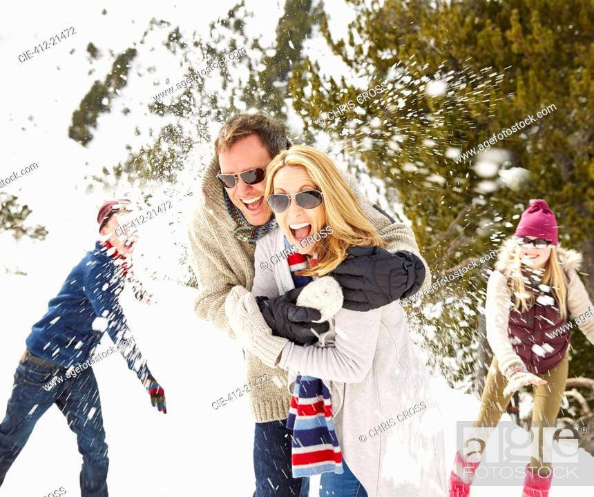 Stock Photo: Family having a snowball fight in the snow.