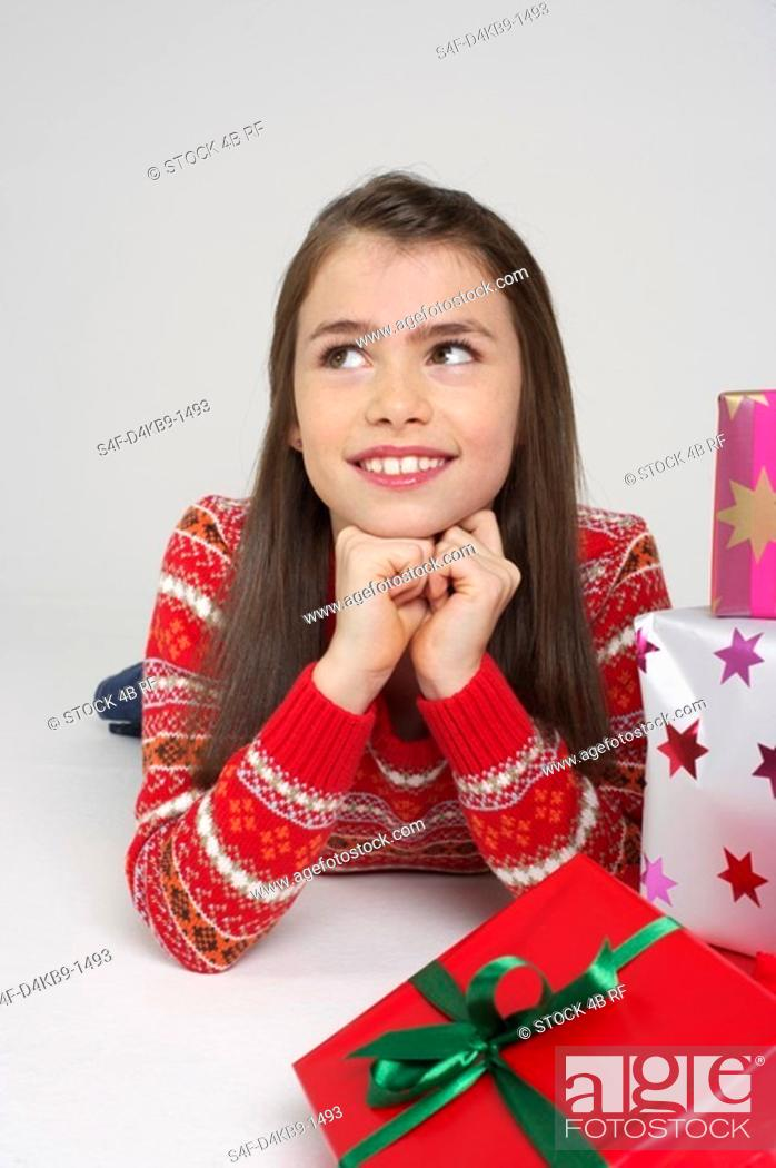 Stock Photo: Smiling girl lying on front next to Christmas presents.