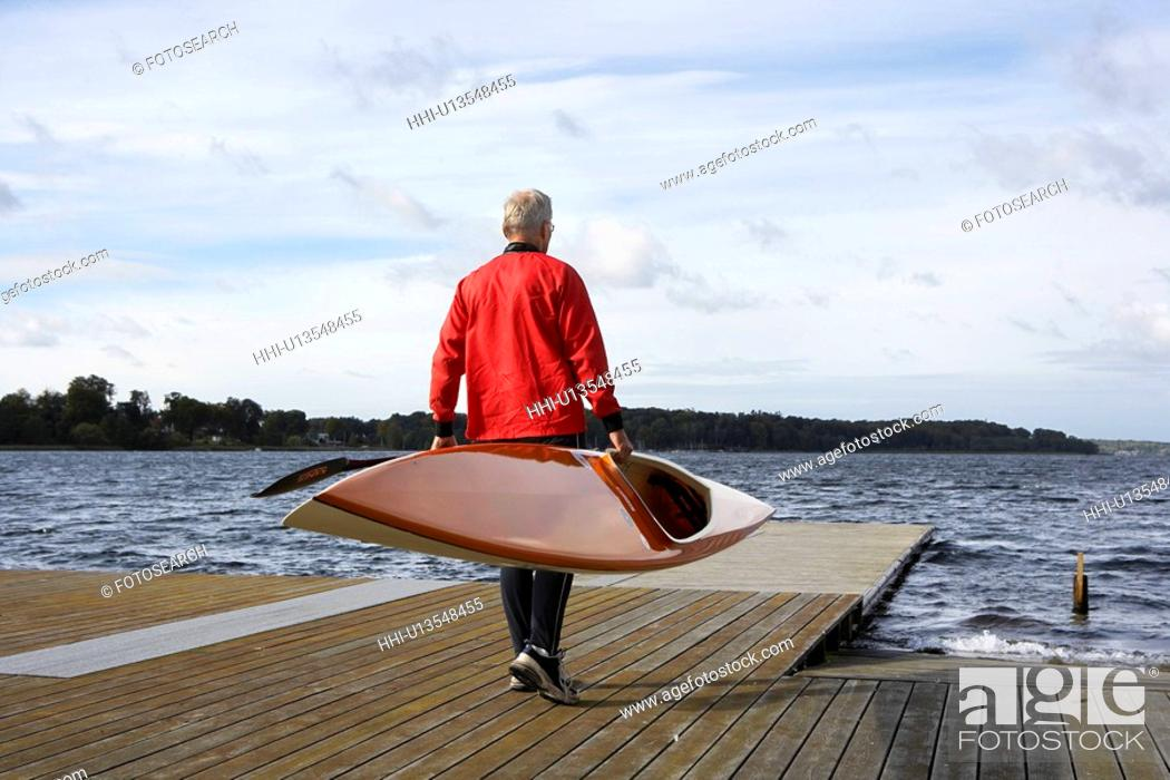 Stock Photo: Senior man carrying a kayak.