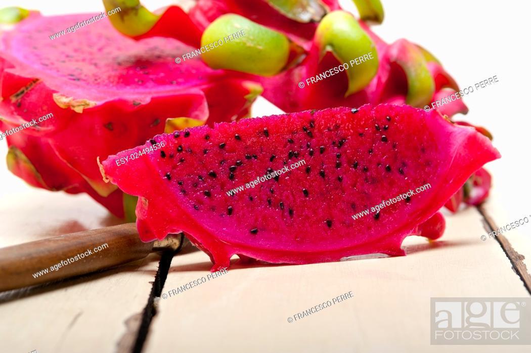 Stock Photo: fresh thai purple dragon fruit over white rustic table.