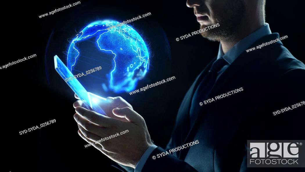 Stock Photo: businessman with tablet pc and earth hologram.