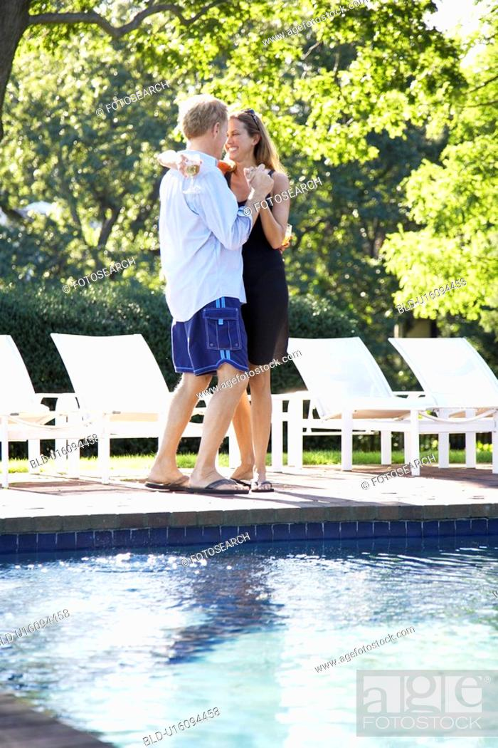 Stock Photo: Couple dancing by pool.