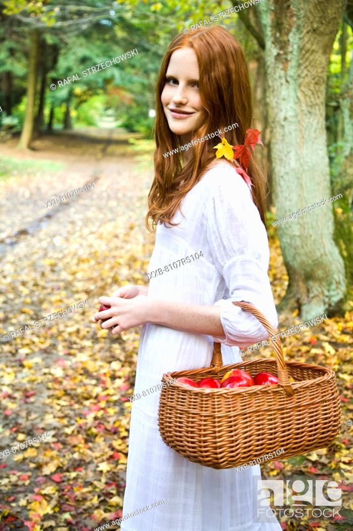 Stock Photo: Ginger woman with basket of apples.