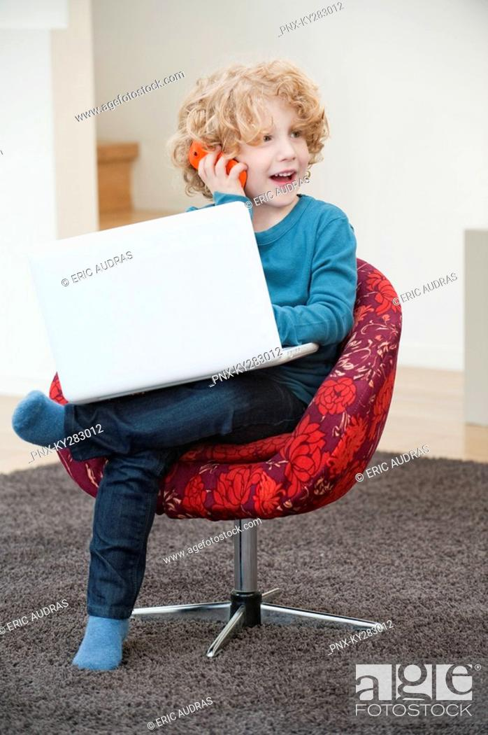 Stock Photo: Boy talking on a mobile phone and using a laptop.