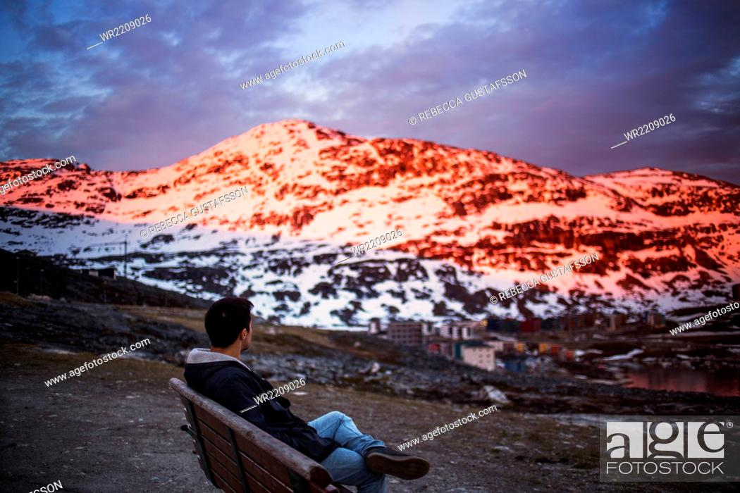 Stock Photo: Side view of young man relaxing on bench with snow covered mountain in background.