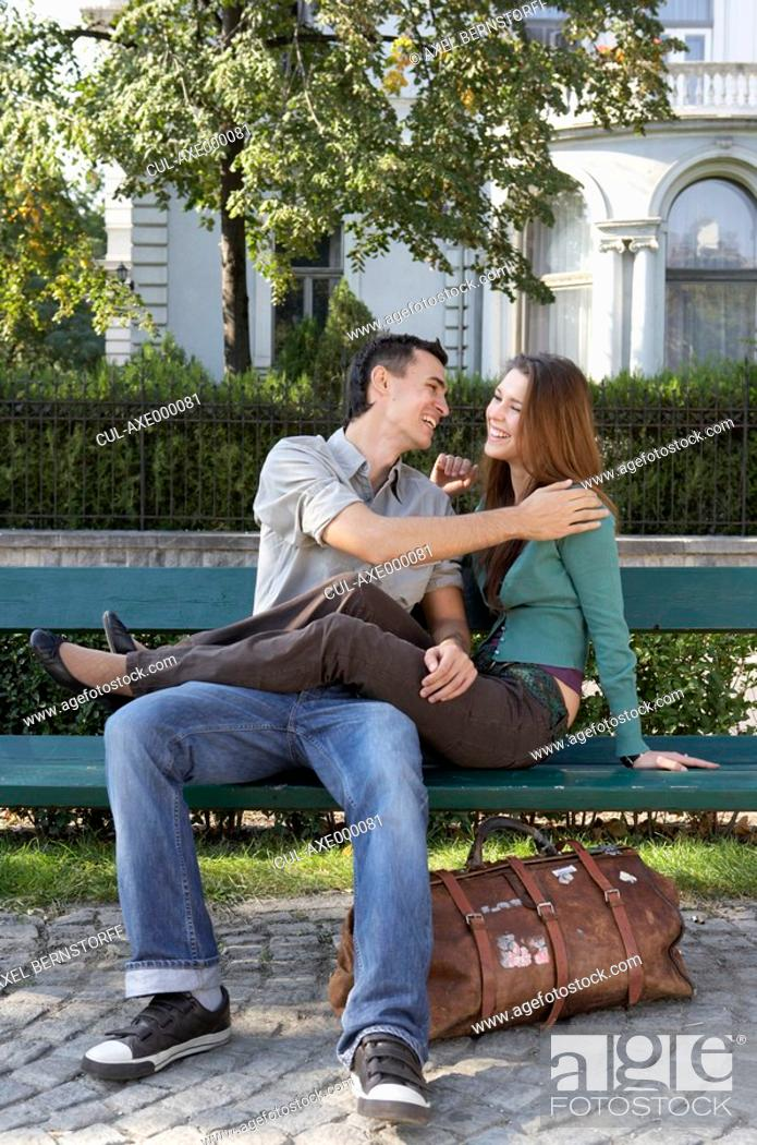 Stock Photo: Couple sitting on a bench laughing.