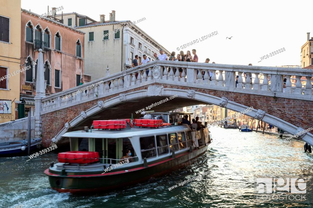 Photo de stock: Venice, Italy - August 1, 2020: Boat used for the public transport of people passes under a bridge (Ponte delle Guglie), while tourists admire the scene from.