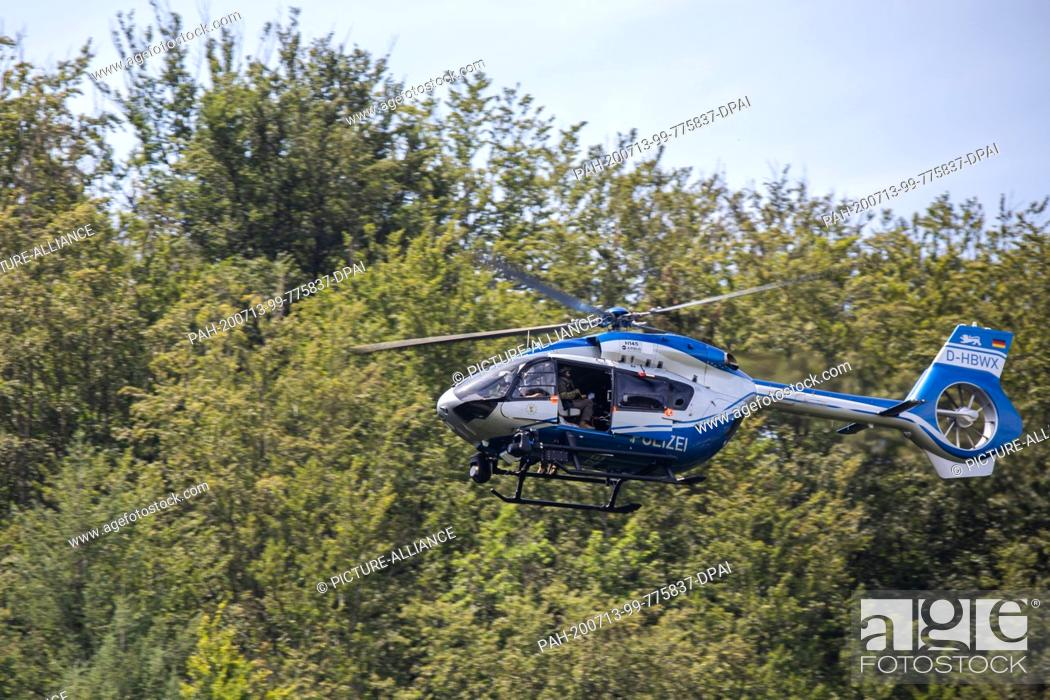 Stock Photo: 13 July 2020, Baden-Wuerttemberg, Oppenau: A police helicopter flies over the forest near the community of Oppenau. The police are searching with a large.
