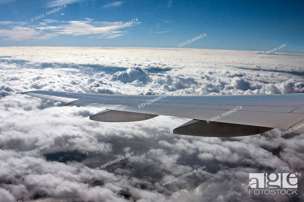 Stock Photo: Airplane wing flying above white clouds.