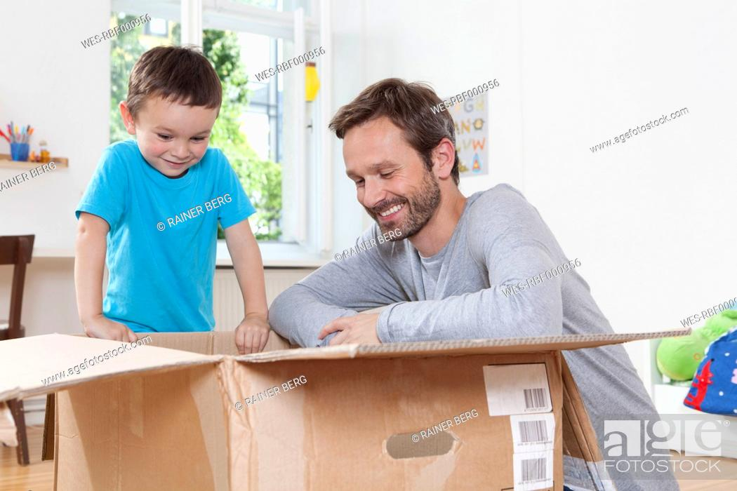 Stock Photo: Germany, Berlin, Father and son opening parcel box.