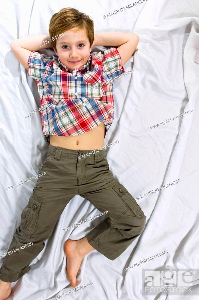 Stock Photo: smiling baby lying on the bed with his arms behind his head.