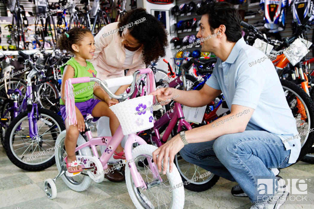 Stock Photo: Parents helping young daughter with bike in bike shop.