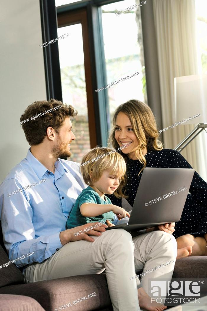 Photo de stock: Smiling parents and son sitting on sofa with laptop at home.
