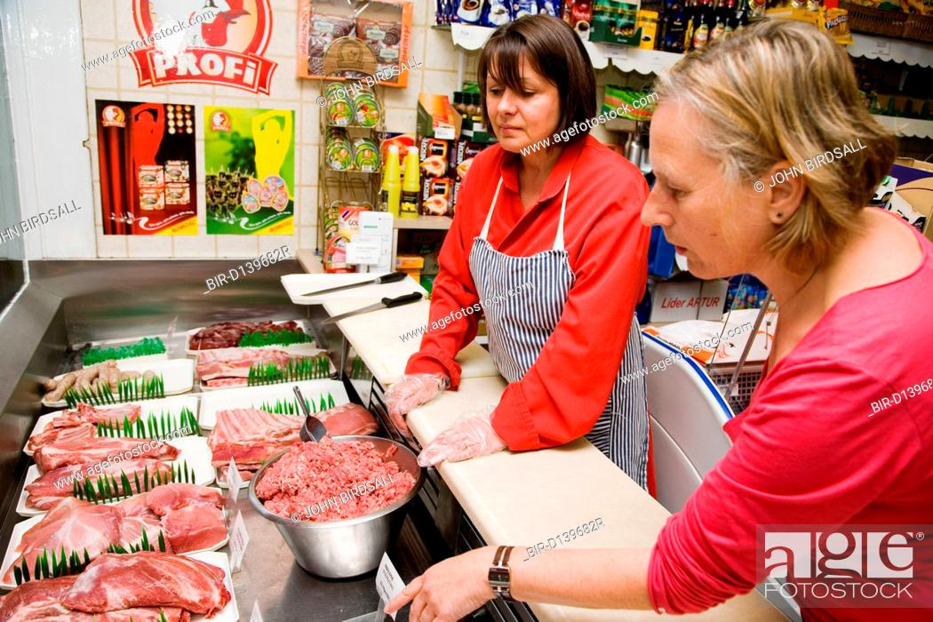 Stock Photo: Customer choosing from various cuts of pork in a Polish continental meats shop,.