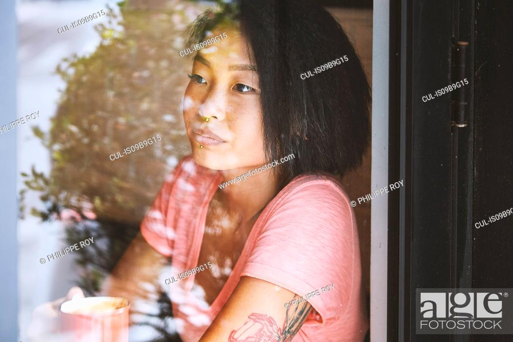 Stock Photo: Woman gazing in cafe window seat, Shanghai French Concession, Shanghai, China.