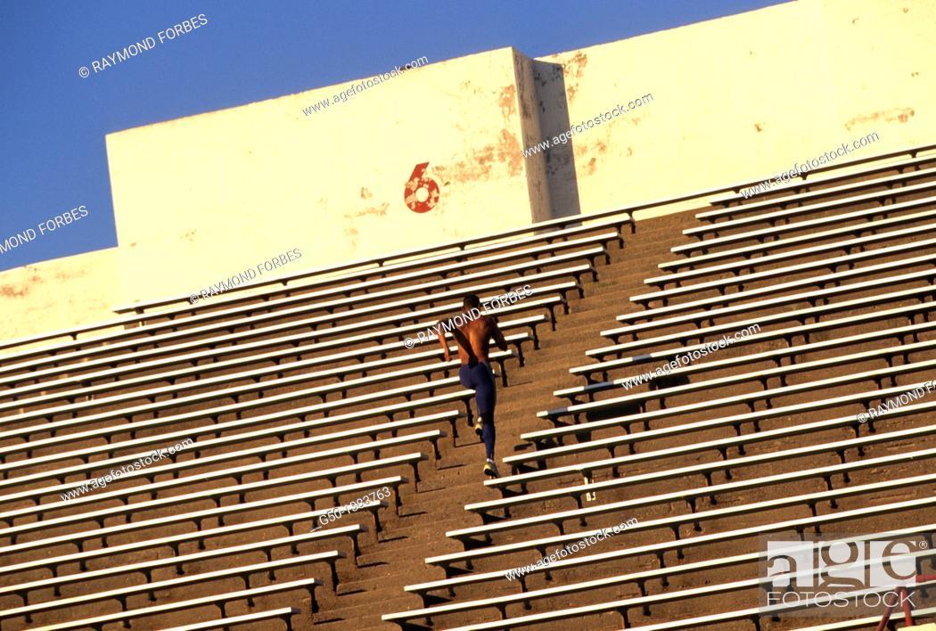 Stock Photo: African American Athlete running in stadium.