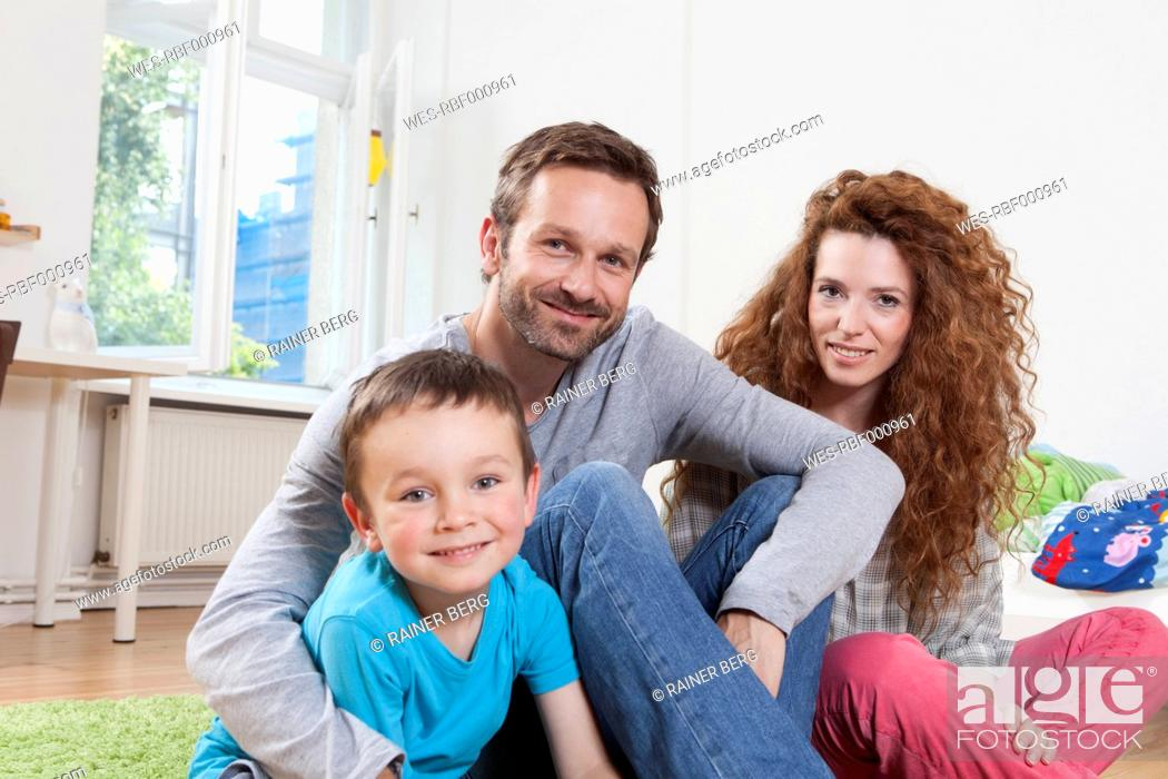 Stock Photo: Germany, Berlin, Portrait of family at home, smiling.