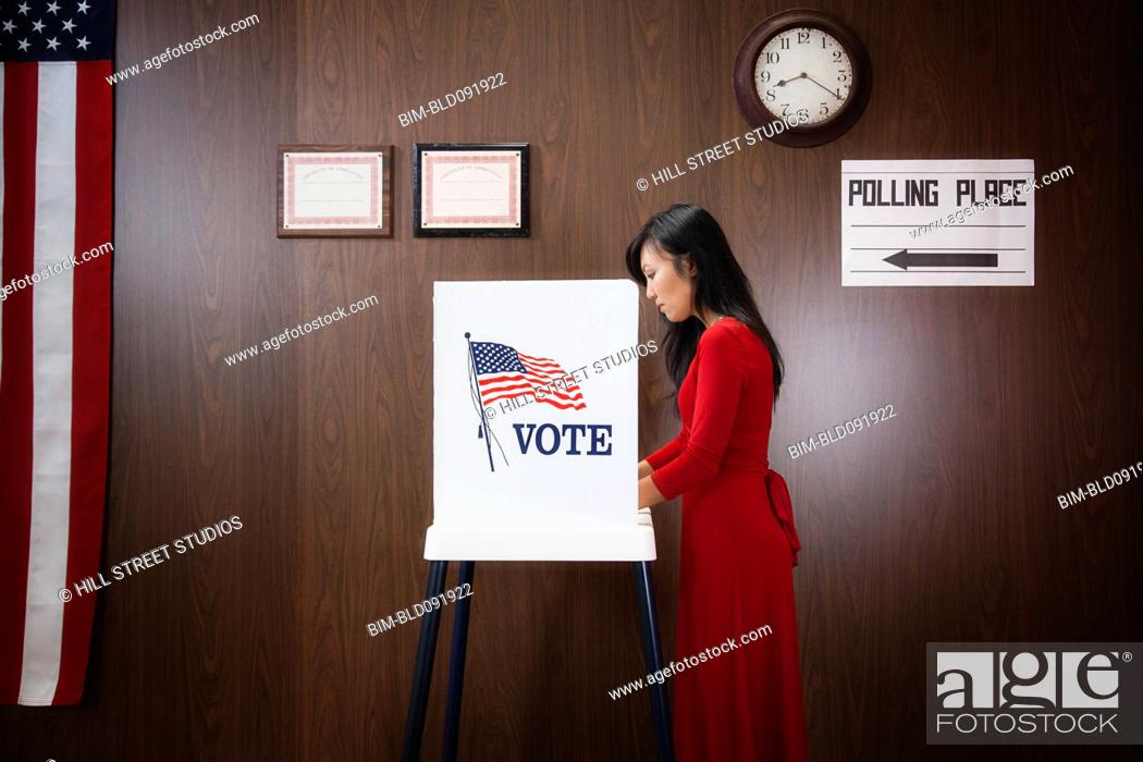 Stock Photo: Asian voter voting in polling place.
