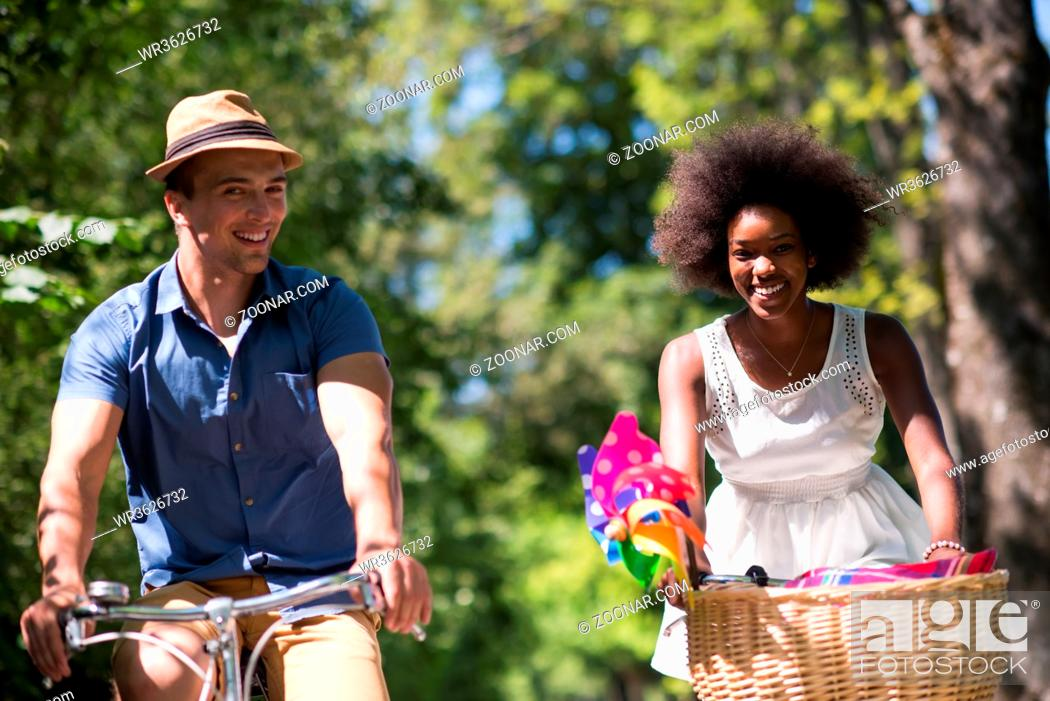 Stock Photo: a young man and a beautiful black girl enjoying a bike ride in nature on a sunny summer day.
