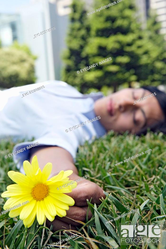 Stock Photo: View of a woman sleeping on the grass and holding a flower.