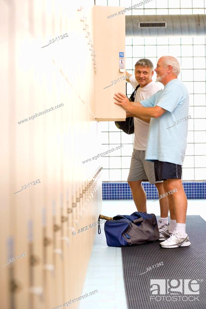 Stock Photo: Two men using lockers in gym, side view.