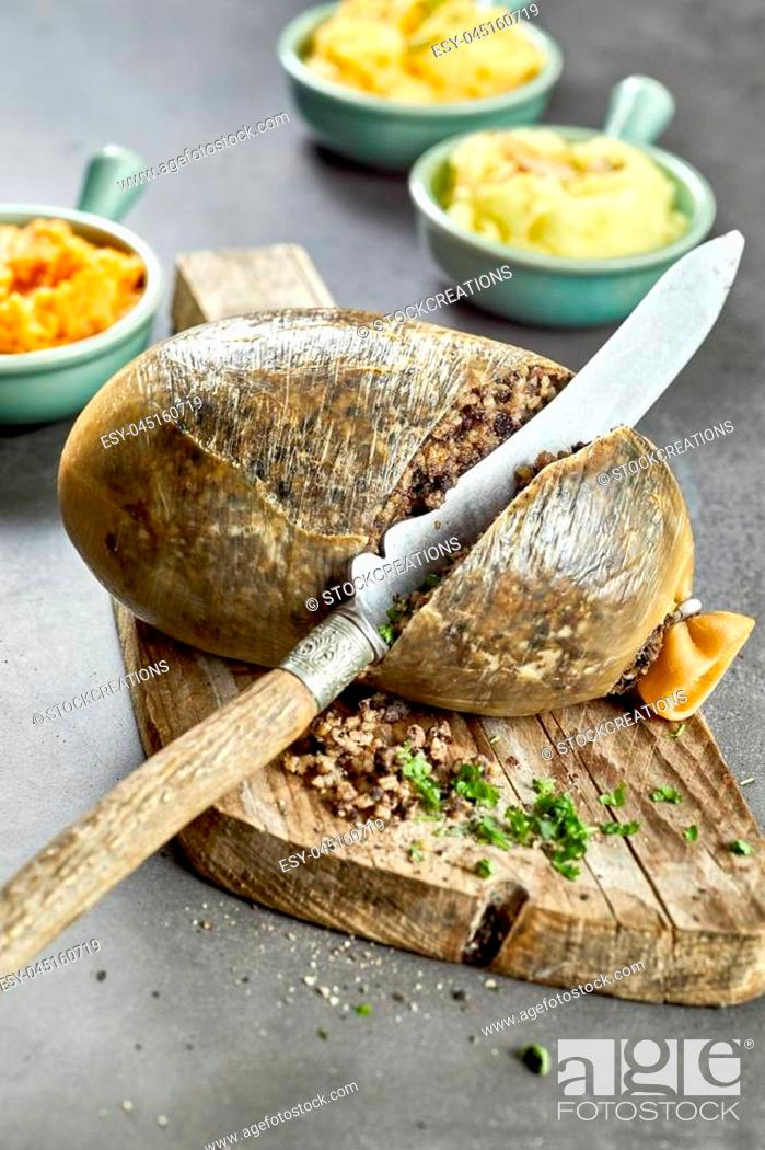 Stock Photo: Slicing open a cooked Scottish haggis made with minced liver, hear and lungs stuffed into a sheep stomach with suet, oatmeal onion and seasoning.