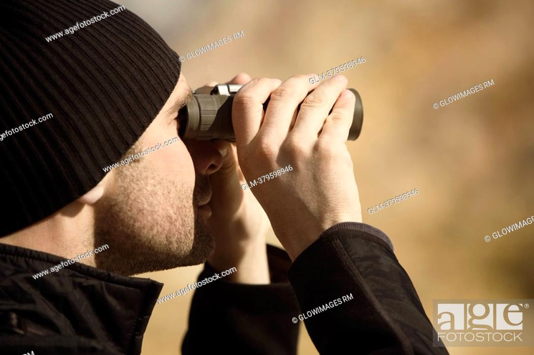 Stock Photo: Man looking through binoculars, Mammoth Hot Springs, Yellowstone National Park, Wyoming, USA.
