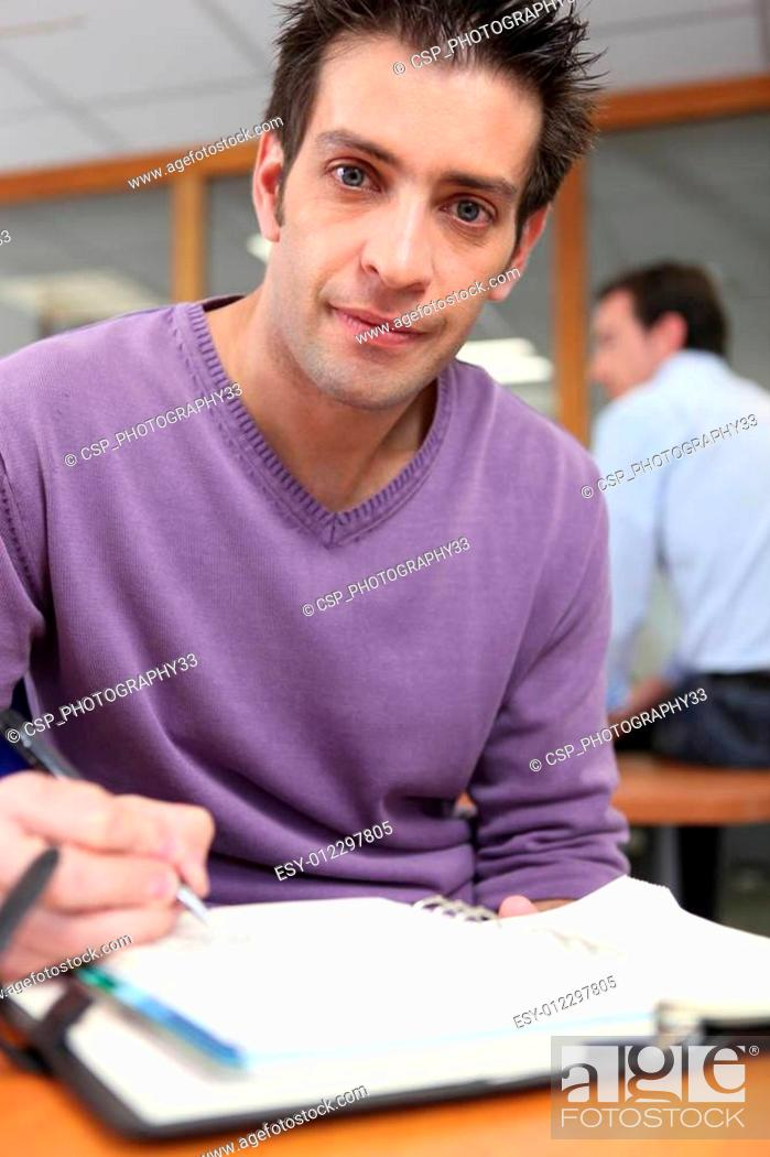 Stock Photo: Casual worker writing in his diary.
