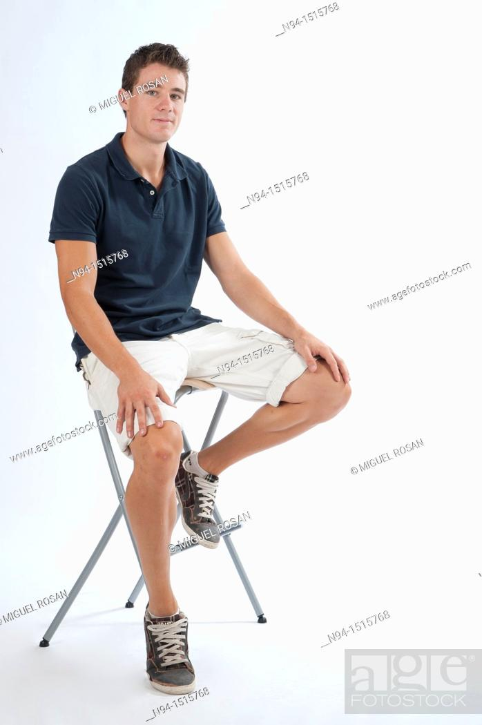 Imagen: Full-body photograph of a teenage boy sitting on a stool.
