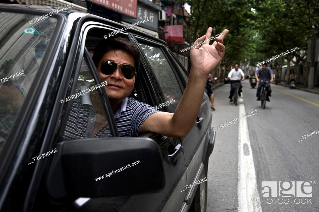 Stock Photo: A taxi driver health through the car window.