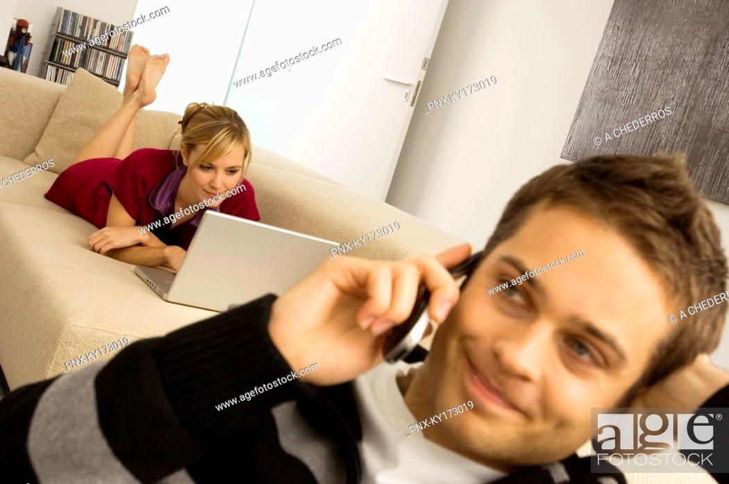 Stock Photo: Young man using a mobile phone with a young woman using a laptop in the background.