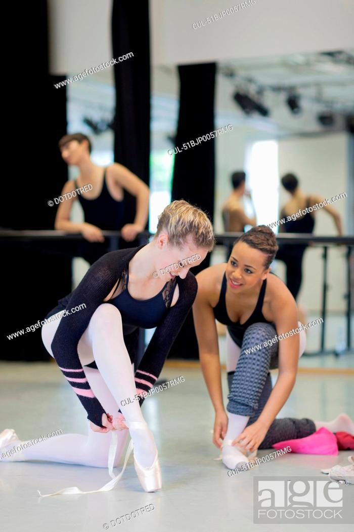 Photo de stock: Ballet dancers tying on pointe shoes.