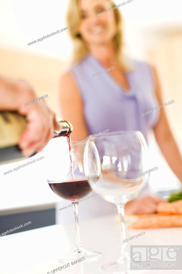 Stock Photo: Couple pouring glass of wine in kitchen.