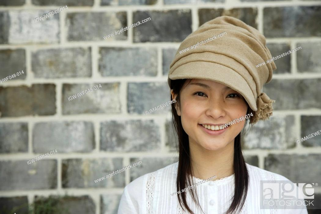 Stock Photo: Portrait of a young woman smiling by brick wall.