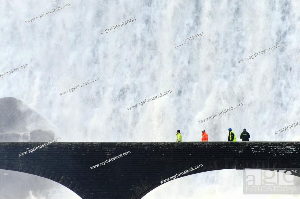 Stock Photo: Elan Valley, Powys, Wales, UK. Visitors walk across a bridge as water cascades over the Caban-coch dam, at Elan Valley village near Rhayader in Powys, Wales, UK.