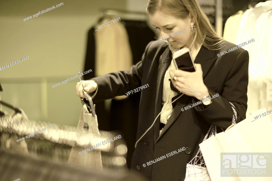 Stock Photo: fashionable woman choosing outfit at clothing store, in Paris, France.